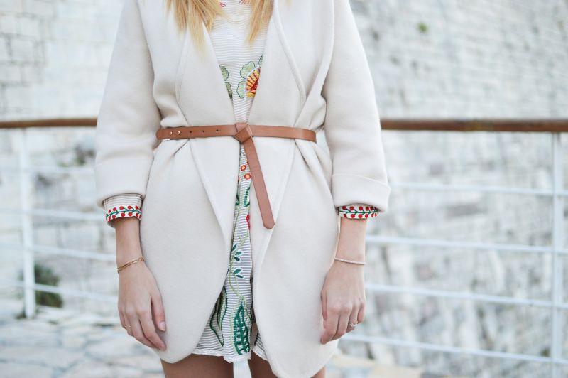 Девушка в белом пальто с ремнем